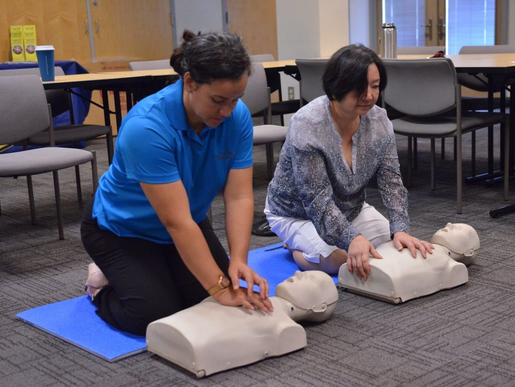 Two women performing CPR on dummies
